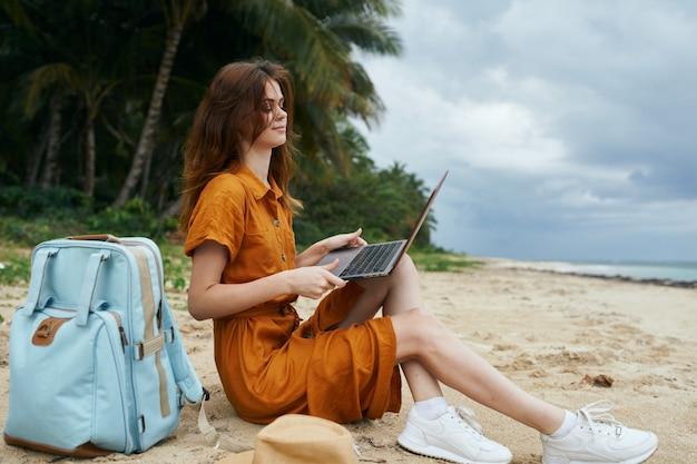 Mulher usando o laptop na praia com palmeiras