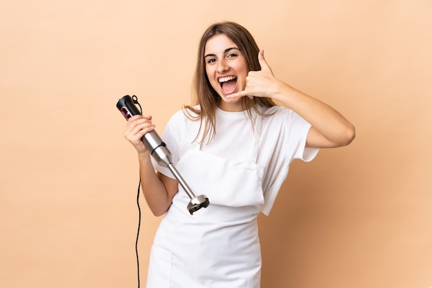 Mulher usando o liquidificador de mão sobre a parede isolada, fazendo o gesto do telefone. ligue-me de volta sinal