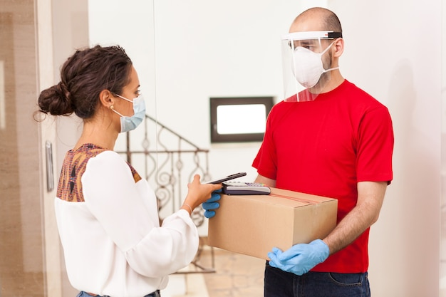 Mulher usando o pagamento por telefone ao levar o pacote do entregador.