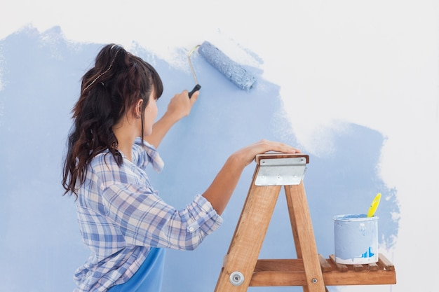 Mulher usando o rolo de pintura para pintar a parede