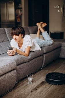 Mulher usando o telefone enquanto o aspirador de pó limpa o chão