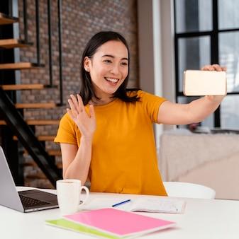 Mulher usando o telefone enquanto participava de uma aula online