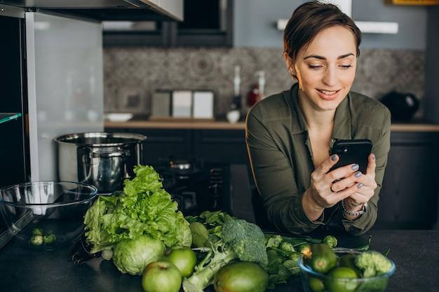 Mulher usando o telefone na cozinha e cozinhando vegetais verdes