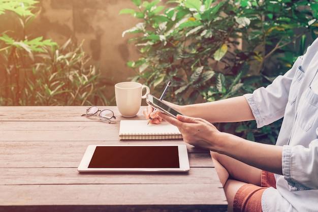 Mulher usando o telefone na mesa de madeira no jardim no café com tonificado vintage.