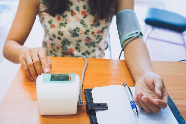 Mulher usando o teste de pressão arterial sozinha.