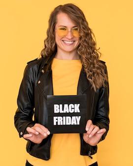 Mulher usando óculos e segurando uma etiqueta preta sexta-feira