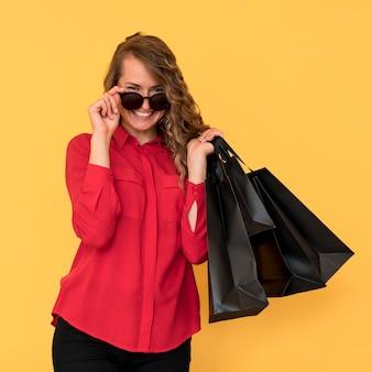 Mulher usando óculos escuros e segurando sacolas de compras