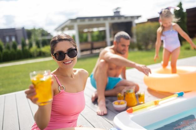Mulher usando óculos escuros. mulher bonita usando óculos escuros bebendo um coquetel gelado enquanto toma sol perto da piscina