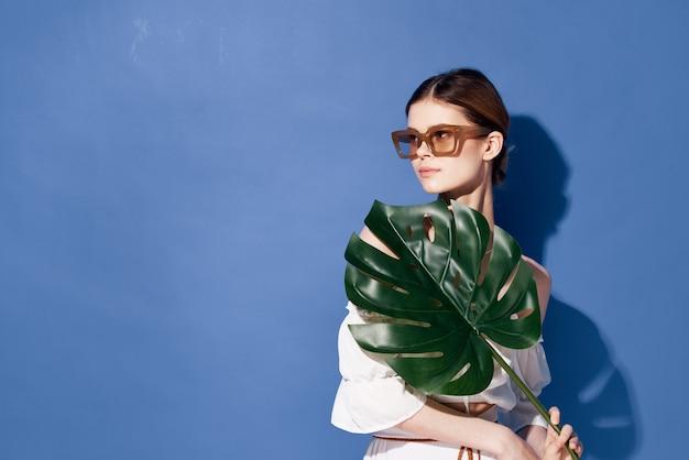 Mulher usando óculos escuros palm cosméticos verão viajar fundo azul.