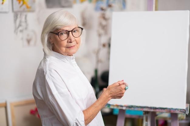 Mulher usando óculos. linda mulher loira aposentada usando óculos antes de pintar na oficina