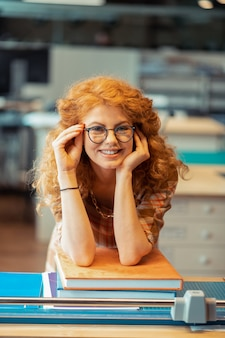Mulher usando óculos. mulher ruiva cacheada usando óculos e sorrindo enquanto está perto de livros
