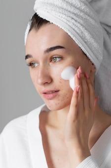 Mulher usando produto para cuidados com a pele