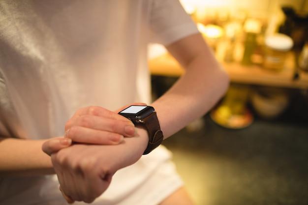 Mulher usando relógio inteligente em casa