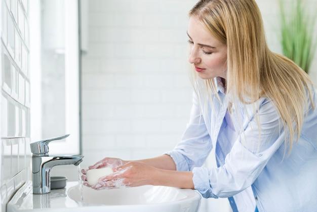 Mulher usando sabão em pó para lavar as mãos