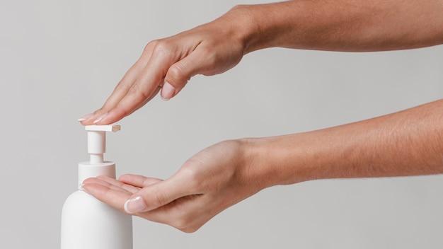 Mulher usando sabonete líquido no banheiro
