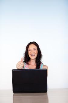 Mulher usando seu laptop com polegares para cima e copyspace