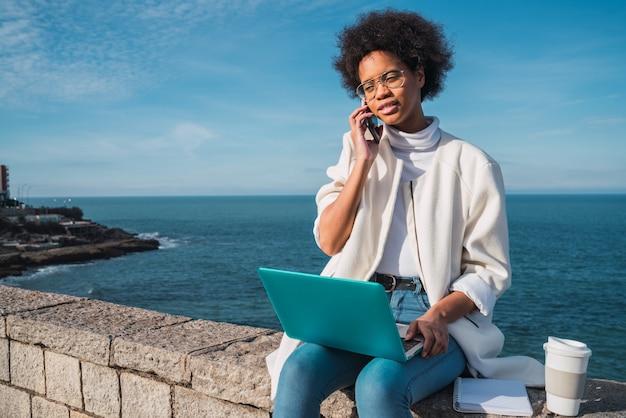 Mulher usando seu laptop e falando no telefone.