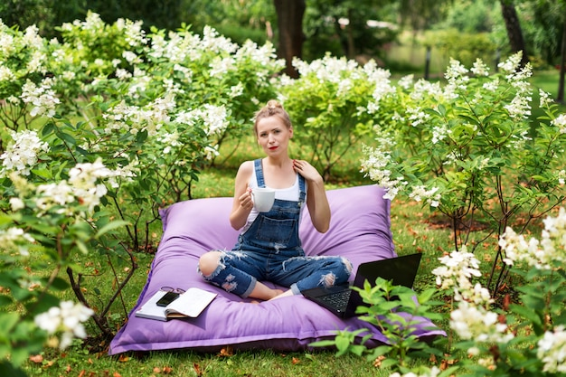 Mulher usando seu laptop no jardim