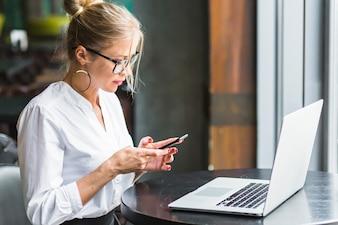 Mulher, usando, smartphone, com, laptop, escrivaninha