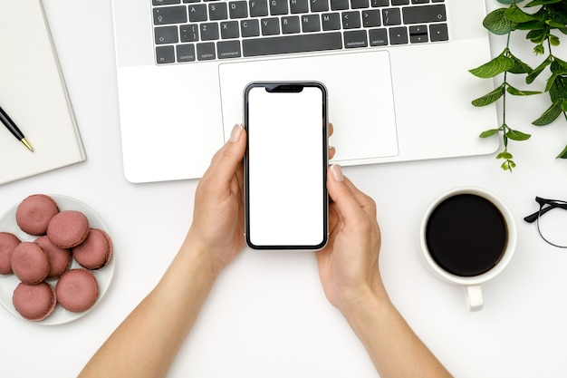 Mulher usando smartphone com tela em branco sobre uma mesa de escritório branca