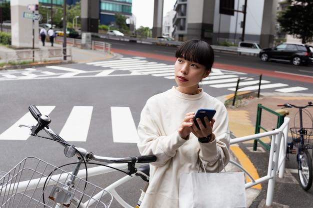 Mulher usando smartphone e bicicleta elétrica na cidade