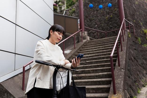Mulher usando smartphone e bicicleta elétrica na cidade Foto gratuita