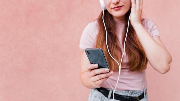Mulher usando smartphone e fones de ouvido para ouvir música