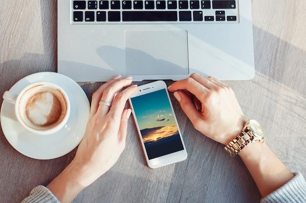 Mulher usando smartphone e laptop no café. jovem garota bebe café e trabalha