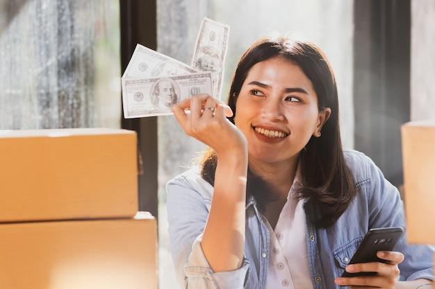 Mulher usando smartphone e segurando as notas de dinheiro sorri com feliz.