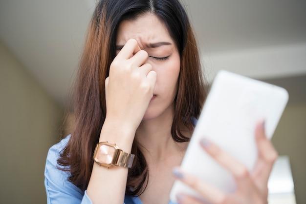 Mulher usando smartphone e sentindo fadiga e dor de cabeça.