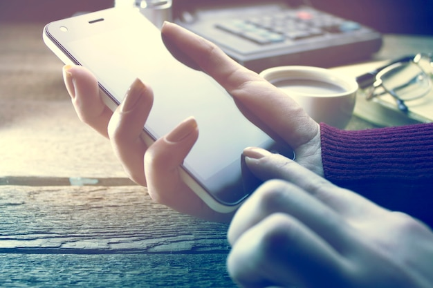 Mulher usando smartphone e xícara de café na mesa de trabalho