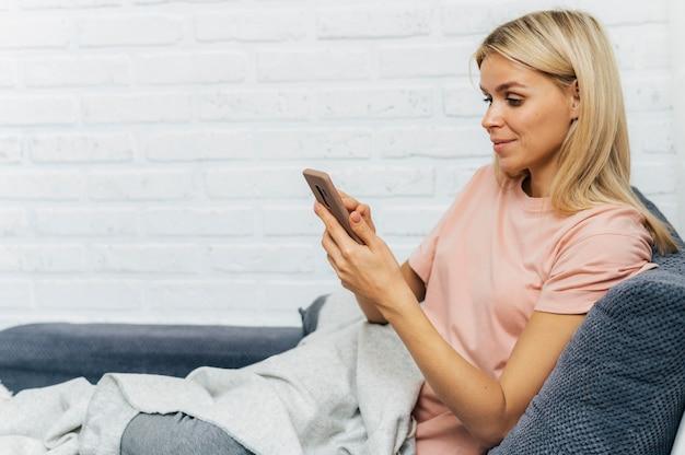 Mulher usando smartphone em casa durante a pandemia com espaço de cópia