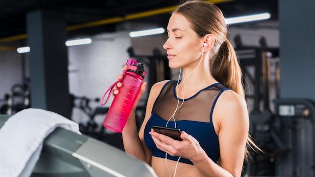 Mulher, usando, smartphone, em, ginásio