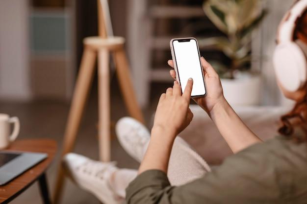 Mulher usando smartphone moderno e fones de ouvido no sofá