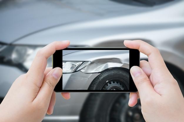 Mulher usando smartphone móvel tira foto acidente de carro