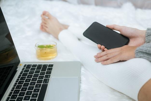 Mulher usando smartphone na cama em um dia frio