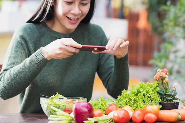 Mulher usando smartphone tirar uma foto comida saudável antes de comer.