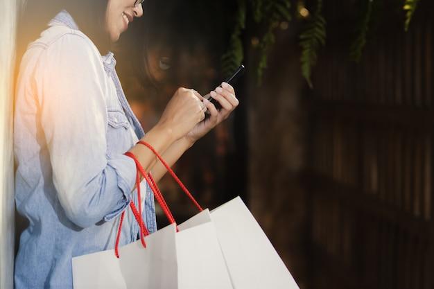 Mulher usando smartphone trabalhando no tempo livre com feliz.