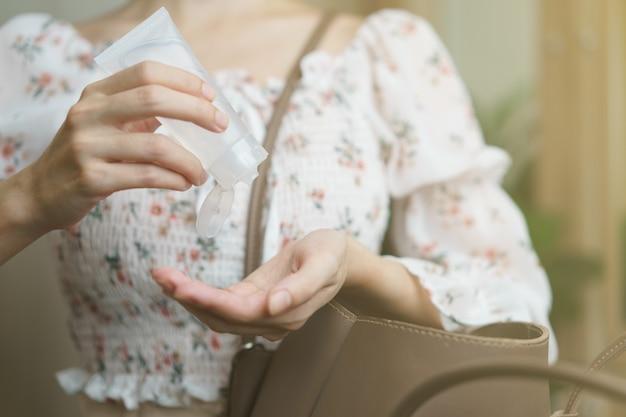 Mulher usando spray desinfetante para as mãos de sua bolsa de mão, prevenção do coronavírus.