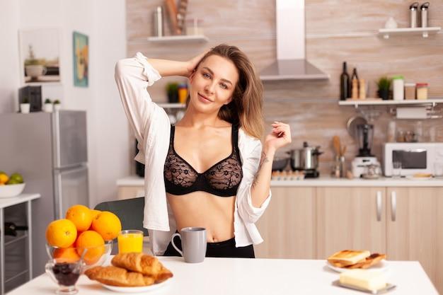 Mulher usando sutiã sexy depois na cozinha de casa depois de acordar desfrutando de uma xícara de café e pão torrado.