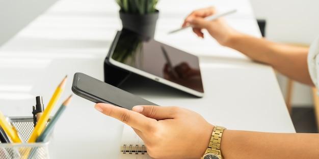 Mulher usando tablet digital e smartphone na mesa