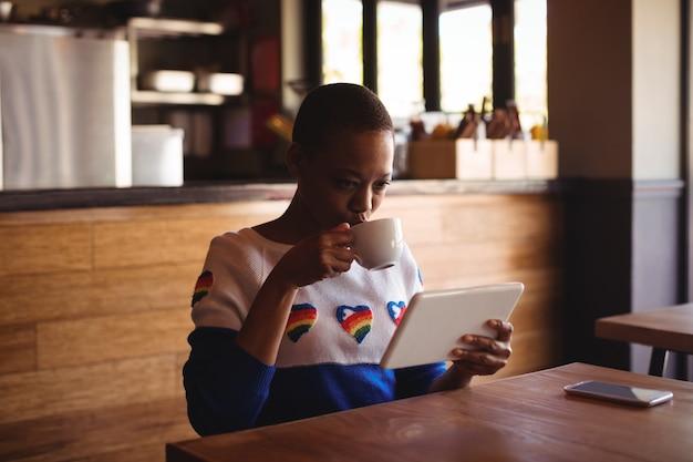 Mulher usando tablet digital enquanto bebe café