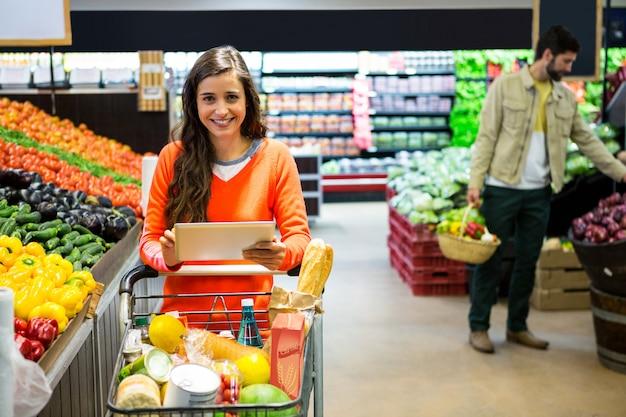 Mulher usando tablet digital enquanto fazia compras no supermercado