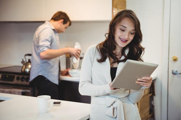 Mulher usando tablet digital enquanto homem trabalha atrás