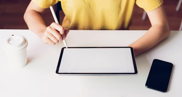 Mulher usando tablet e smartphone em cima da mesa, simulado acima da tela em branco.
