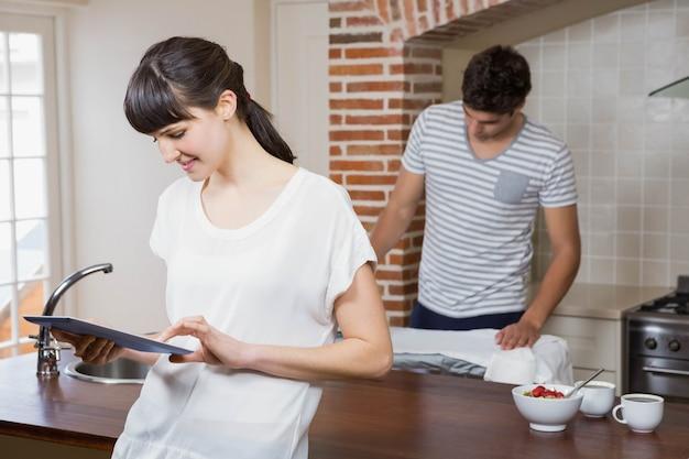Mulher usando tablet na cozinha enquanto homem passando uma camisa
