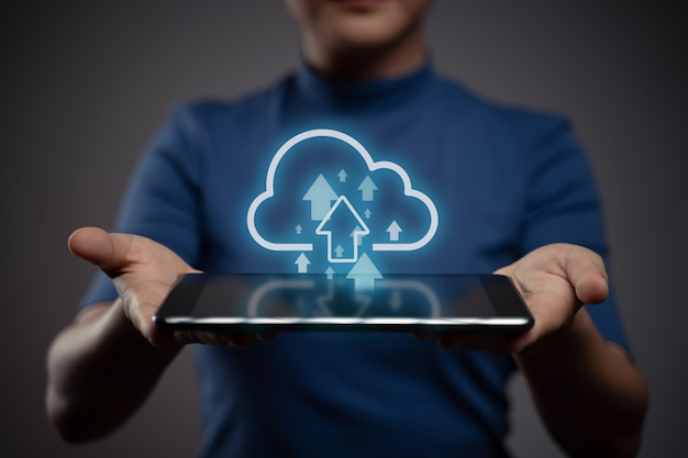 Mulher usando tablet para fazer upload com efeito de holograma de ícone de nuvem