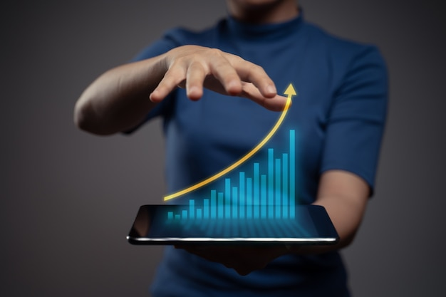 Mulher usando tablet, planejando marketing digital com efeito de holograma gráfico