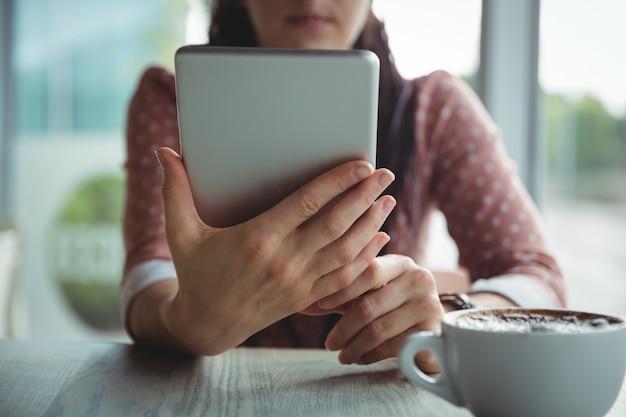 Mulher, usando, tablete digital, enquanto, tendo, xícara café