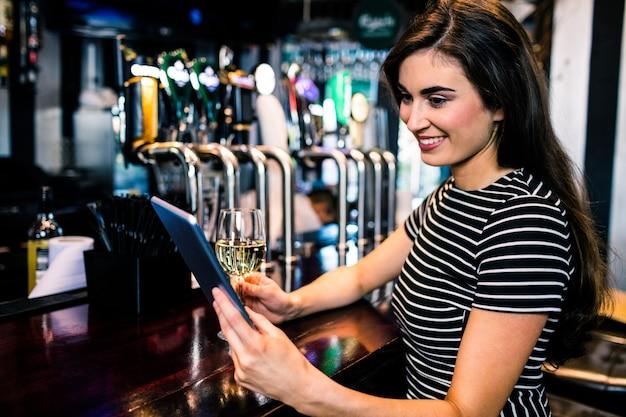 Mulher, usando, tabuleta, e, tendo, um, vidro vinho, um bar